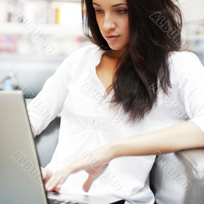 Portrait of a beautiful young woman working on laptop while sitt