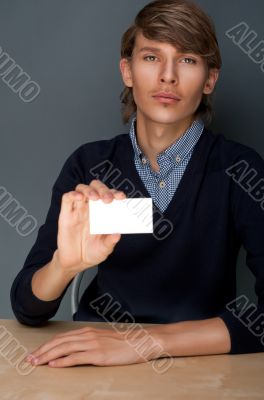 Portrait of young handsome business man holding blank white busi