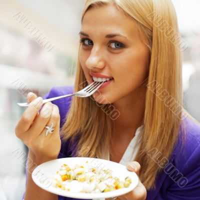 Closeup portrait of an attractive young woman eating fruit salad