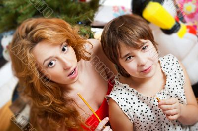 Mother and her daughter sitting together near christmas tree. To