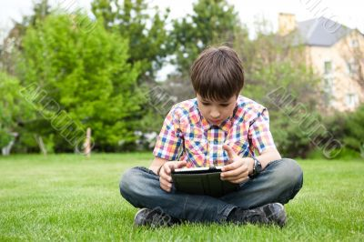 Young boy outdoors on the grass at backyard