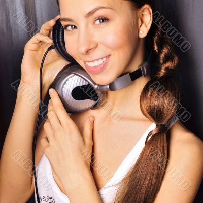 Club style woman with headphones listening to music