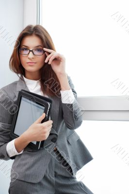 Smiling young business woman using tablet PC while standing rela