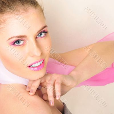 Beautiful woman in pink color scarf against white wall