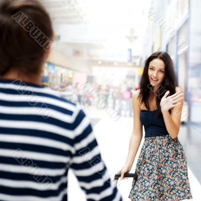 Young man meeting his girlfriend with opened arms at airport arr