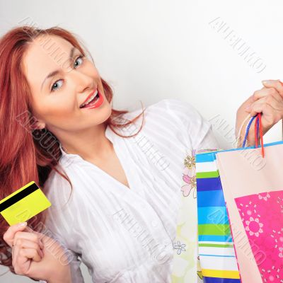 Beautiful shopping woman holding bags and credit card at a mall