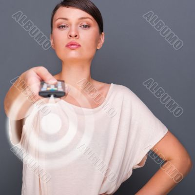 Portrait of a beautiful fashionable elegant woman with remote co
