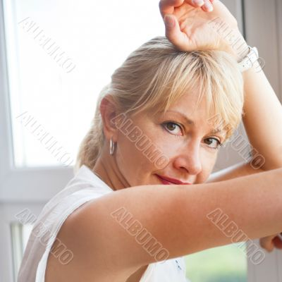 Closeup portrait of smiling woman standing near big window