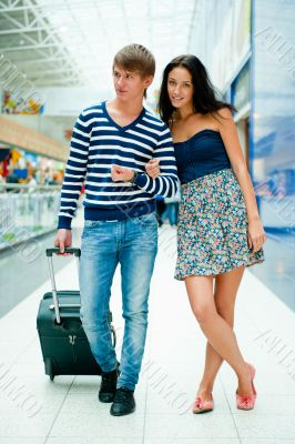 Full-length portrait of young couple in love walking with suitca