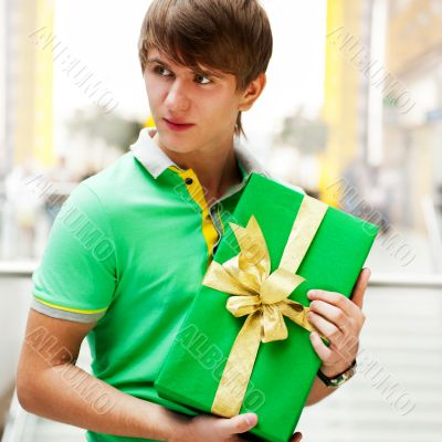 Portrait of young man inside shopping mall with gift box standin