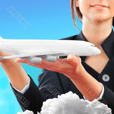Portrait of young happy woman stewardess holding jet aircraft in