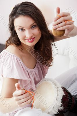 Happy young pretty woman at home, smiling and playing arabic tra