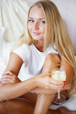 Woman drinking fresh ice tea beverage and looking at camera whil