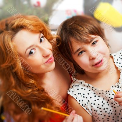 Mother and her daughter sitting together near christmas tree