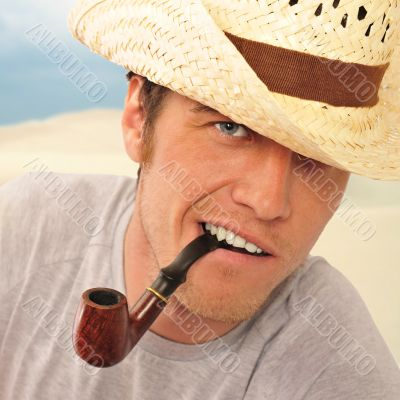 Closeup of a happy brutal young man looking at camera and smokin