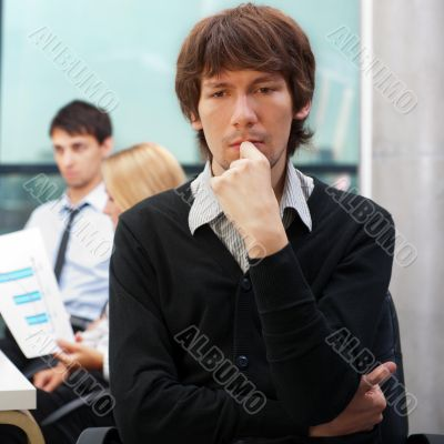 Portrait of a young business man sitting by his laptop in the of
