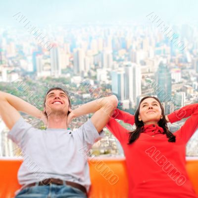 Closeup portrait of adult couple sitting on their sofa against b