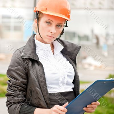 Young architect-woman wearing a protective helmet standing on th