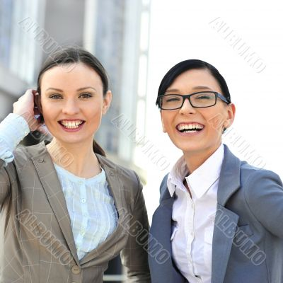 Portrait of two businesswomen outside.