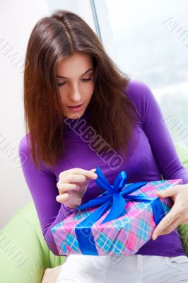 Delighted woman opening a gift sitting on the bean bag at home