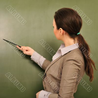 Portrait of young woman teacher standing near blackboard and exp