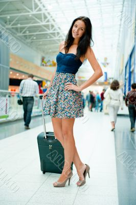 Young pretty stylish woman with luggage at the international air