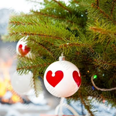 Christmas baubles against burning flame in fireplace on christma