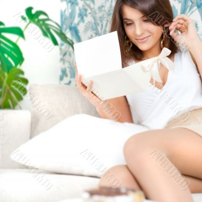 Delighted woman reading a greeting card sitting on the sofa at h