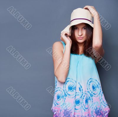 Confident woman with arms near her head holding hat against a bl