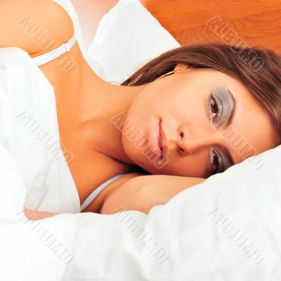 Fashion portrait of young elegant woman in bed