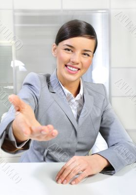 Business woman gives a handshake at her office. Vertical shot.
