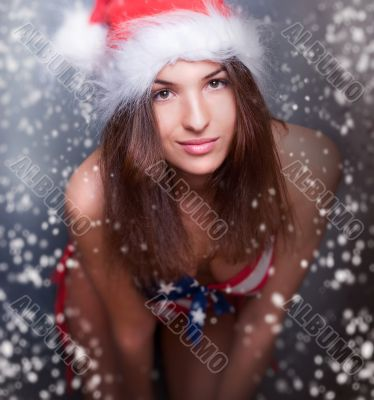 20-25 years old beautiful woman in christmas hat and swimsuit wi