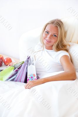 Young happy attractive girl unpack shopping bags in bedroom or h