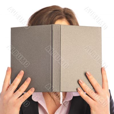 Young smiling student woman hiding under book. Over white backgr