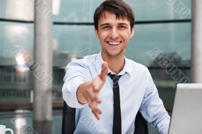 Happy mature business man offering a welcoming hand