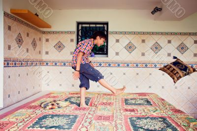 Artistic lifestyle photo of young boy kicking pillow standing on
