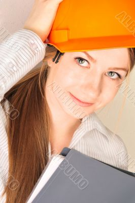 Closeup portrait of young pretty engineer woman wearing helmet