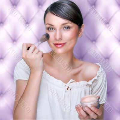 Portrait of attractive young adult woman applying blusher agains