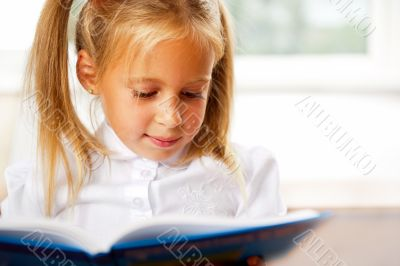 Image of smart child reading interesting book in classroom