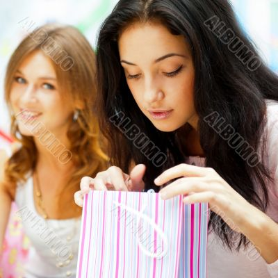 Two excited shopping woman resting on bench at shopping mall. Lo