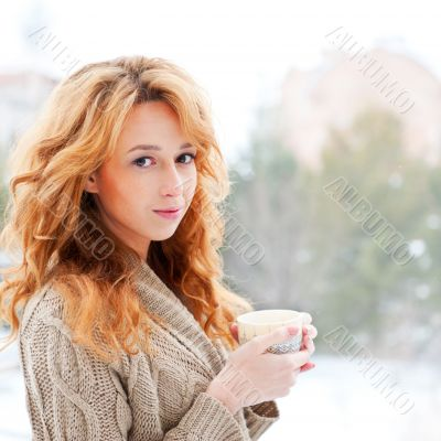 Portrait of beautiful red hair girl drinking coffee on winter ba