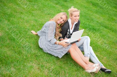 Portrait of two smiling women using laptop on a green meadow at