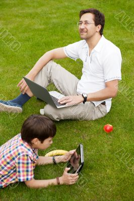 Man and young boy his son sitting outdoors