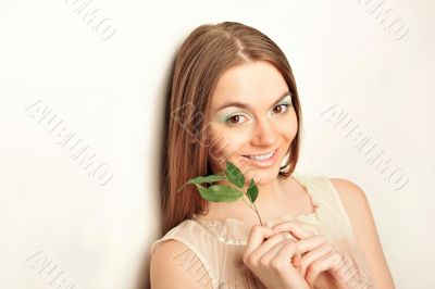 Portrait of young pretty woman holding green leave