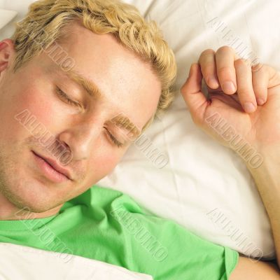 A peaceful man in his bed before waking up in his bedroom