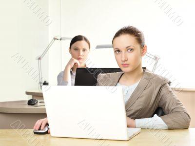 Portrait of two women working at their desks