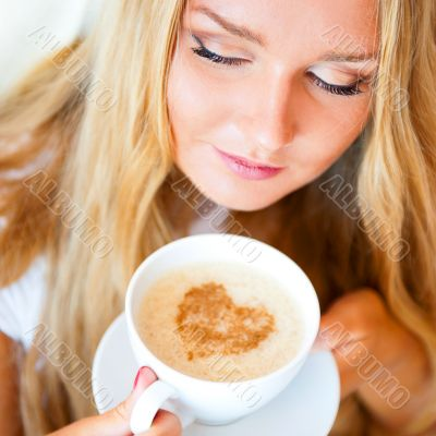 Smiling woman drinking a coffee lying on a be