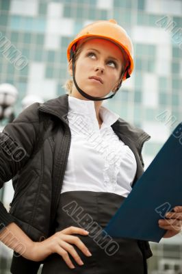 Young architect-woman wearing a protective helmet standing""