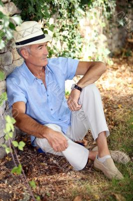 Mature man resting along a wall.
