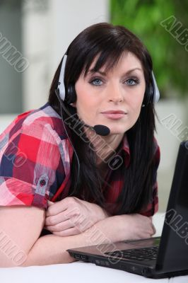 Woman laid in front of laptop with headset